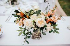lush wedding centerpiece of white garden roses, peach stock, white majolik spray roses, blush rice flower, eucalyptus greenery, magnolia, privet berry and chamomile on mercury glass pedestal.