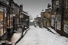 WEST YORKSHIRE – Haworth village, England, Great Britain, UK. This is an older picture of Haworth looking towards the south on Main St. All the shops, as well as the store fronts, are different now. Brontë Parsonage Museum is located in this village. Haworth itself is located 16.5 miles (26.5 kms.) west of Leeds. https://www.google.ca/maps/place/72+Main+St,+Haworth,+Keighley+BD22,+UK/@53.8310359,-1.9597643,16z/data=!4m5!3m4!1s0x487bee95dfc166cd:0xc0529655a07b8c54!8m2!3d53.8310359!4d-1.955387