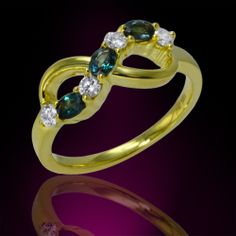Crafted in 18K gold, this infinity ring features three oval shape natural alexandrites set in prongs and accented by an assortment of round shape diamonds.