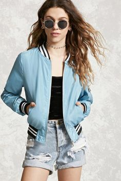 A woven bomber jacket featuring a zip-up front, varsity stripes on ribbed trim, two front slanted snap-button pockets, a zippered pocket on one arm, and long sleeves.