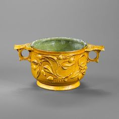 Roman yellow glazed pottery skyphos, 1st century A.D. With a pomegranate branch in relief, 8.4 cm high. Private collection