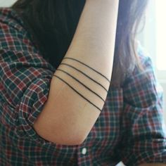 Apparently these were traditionally symbols of a dead family member. When someone close to you died, you got a black line on your arm. Recently I've seen them on thighs, lower and upper arms, and biceps.