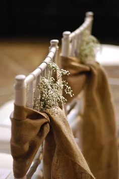 Chairs tied with burlap bows & a little baby's breath