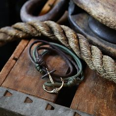 Beautiful Wood Beam Anchor Bracelets with waxed cord. The combination of military cord, waxed cord, metal, and wood gives this bracelet a very earthy and rustic feel. This one-size-fits-all anchor bracelet features our Maritime Anchor in a copper/bronze casting paired with our hand waxed brown cotton cord and our Green military spec cord. Each wooden stock on this anchor bracelet is handcrafted, finished, and sealed with a mahogany red stain presenting a new level of vintage authenticity.