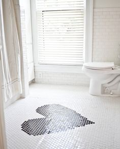 In this bathroom, penny-round tiles were used to create a large black heart, offering a graphic hit that's girlie but not too sweet.