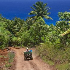 A woman drives an ATV down one of the Pitcairn Island's dirt roads. There are no cars on the island. Coastalliving.com