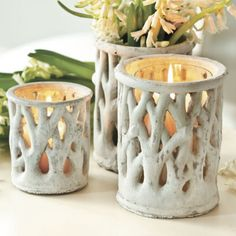 The pierced design allows candlelight to filter between the faux bois branches, casting romantic shadows.