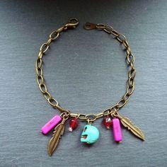 """Bracelet grigri 1 - tête de mort, pierres précieuses  fuchsia, plumes et chaîne laiton bronze. Signé """"les bijoux de Miss poisson rouge""""."""