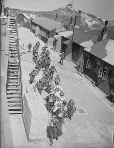 ATS girls and gun crews of 177 Heavy Battery rush to 'take post' at Fort Crosby near Liverpool, England. This training operation formed part of British preparations to repel the threatened German invasion of 1940.