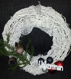 """Dörrkrans dekorerad med julgranskulor, fåglar och pin med """"Välkommen"""" som text."""