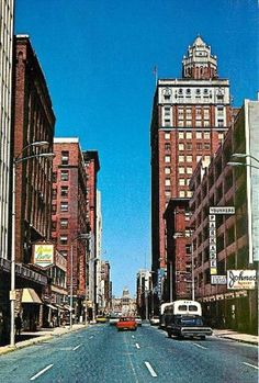 Downtown Des Moines, 8th and Locust, looking East 1965. Des Moines Register and Tribune and Bishops Buffet are on the left [ north side of street]. The old Younkers Parkade [parking ramp] is on the south side.