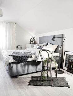 A Scandinavian bedroom, awash in cool tones, soft textures, bright light.