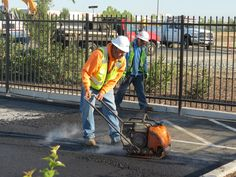 Compacting new asphalt in tight spaces during a parking lot paving operation in West Sacramento, Calif.