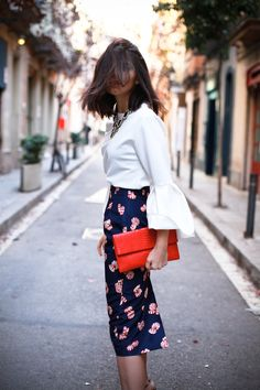 Statement necklace, white blouse, blue printed pencil skirt, and red clutch