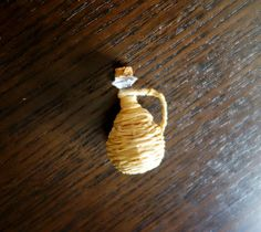 El material es muy sencillo: rafia, un trocito de corcho, una cuenta de madera, una chincheta y aguja         Lo primero es dividir la ra...