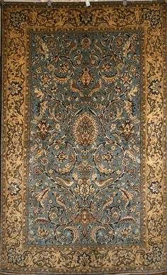 A muted blue Persian Qum rug with birds and tree of life design.