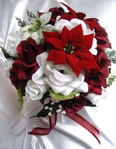 Winter Bridal Silk Bouquet Red poinsettia, white roses, white poinsettia, burgandy roses, accented greenery, hand tied with burgandy ribbon. Contact us for custom orders.