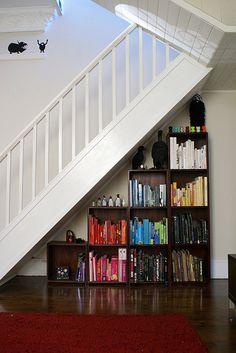 Chromatic bookshelf under the stairs