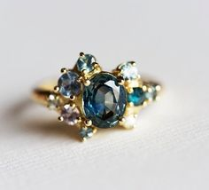 Beautiful teal bi colour sapphire cluster ring. ★Product details Main stone Gemstone type: approx. 1.1 ct bi colour teal blue green sapphire (The sapphire is natural therefore it can vary in colour, shape and size a little.) Side stones Blue to light blue sapphires: approx. 1.75-3 mm (4)