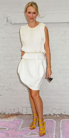 Naomi Watts in an all-white dress paired with golden-yellow strappy sandals.