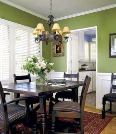 Rich green walls in a dining room coordinate well with a periwinkle blue kitchen, visible through the doorway. It's often necessary to consider how two colors in adjacent rooms will look next to each other, whenever both can be seen at once from a single vantage point.