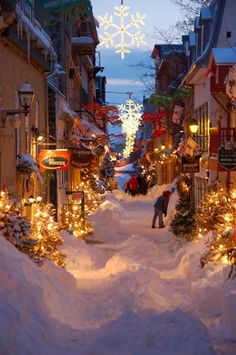 Quebec City ~ Alain Hebert.  The Petit Champlain street, a pedestrian street,were some artisanal and commercial shop invite tourist all year round to by some souvenir of our beautifull city.Was taken after a 40cm snowstorm the pedestrian path are still there and lightening of each store glow on the fresh snow on the ground.It seem to be in the old past time when each store owners have to clear the path in front of their store.