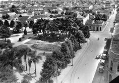 Outro canto da Praça Osório, com a Rua Voluntários da Pátria. O curitibano apelidou o conjunto de cedros que aparece na esquina como Bosque Vienense. Um tufão acabou com a poesia do bosque em 1940, derrubando todas as árvores.