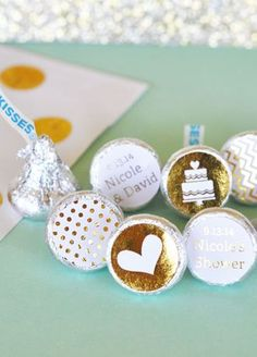 """Offer some love and """"kisses"""" to your guests with these Personalized Metallic Gold & Silver Foil Hershey's Kisses Labels! These metallic labels are sure to add glitz & glam to a favors. Apply these labels to the bottom of your favorite Hershey's Kisses or other candies and display them in a bowl at your special event.  Features and Facts:  Each set contains 108 shiny metallic foil labels with a TRIO of designs - one pattern, one silhouette design and one with personalized text."""