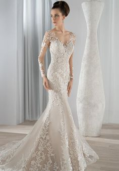 This timeless lace fit n flare gown features an illusion scoop neckline and long sheer sleeves. The dramatic low illusion back is finished with button closures and a Chapel train.