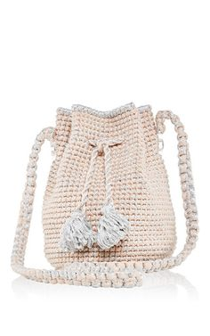 This **7II** bucket bag features a hand woven pink and sparkly silver body with tassel drawstring closure, round transparent plexiglass bottom, inside pocket, and a long macramé handle.