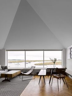 Once inside, a staircase leads up to a large living, dining and kitchen space in the larger white volume, with windows looking north, out towards the sea. British Architecture, Residential Architecture, Living Area, Living Spaces, Two Bedroom House, Dark Wood Floors, Minimal Home, Wooden Doors, Norfolk