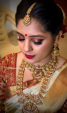 Monica looks gorgeous for her muhurtham. The red and gold colours are bridal perfection. Hair and makeup by Vejetha for Swank. South Indian bride. Indian bridal makeup. Bridal MUA. Red lips. Eye makeup on fleek. Bridal gold jewellery. Maang tikka. Jhumkis. Winged eyeliner.