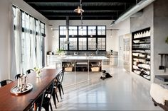 Long and narrow dining space in spacious loft with industrial kitchen