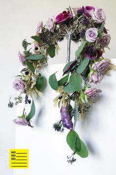 A two heads cascading silver frame holds an abundance of delicate lavender roses spiced up with purple beans and pods. The Trachelium, Lavander and Eucalyptus give the elegant bouquet a sort of boho/provencal appearance which gets elevated by the rich violet Phalaenopsis orchids. It's a romantic yet modern bridal bouquet meant for an boho wedding with a contemporary approach.