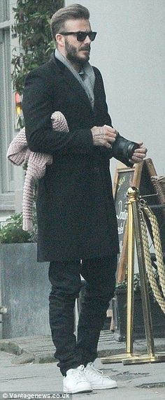Stylish: David, who is no slouch in the fashion department was handsome in black jeans and a black coat, along with a grey scarf and trainers