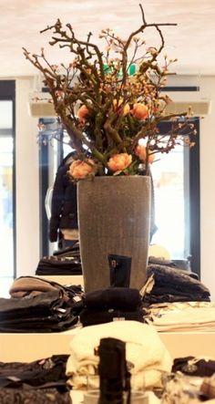 Mooie stevige vaas met decoratietakken en zijde bloemen eyecatcher in een kledingzaak, makkelijk in onderhoud. www.decoratiestyling.nl