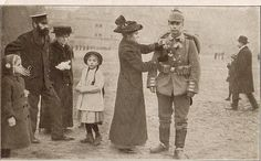 """A mother pins flowers, the traditional gift to German soldiers leaving for war, to the jacket of her son."""