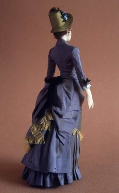 Carabosse Dolls  NAME: Brigitte  PERIOD: 1884-1887  PRICE: 550 euros  Walking dress in blue douppion silk with golden sheen. Walking stick made out of wood with handle in golden silver. http://carabosse-dolls.com/web/c_images/fotos/g-brigitte-tr.jpg