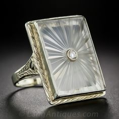 Vintage 14k Quartz and Diamond Ring This sleek and substantial 1930s Depression-era ring features a central rectangular plaque of carved quartz, pierced in the center with a bright and sparkling brilliant-cut diamond, and set in a 14k white gold Art Deco ring with pierced shoulders and touches of hand-engraving.