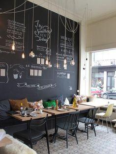 Modernen und fröhlichen Coffee-Shop Dekor mit einer Tafel Wand und hängenden Glühbirnen