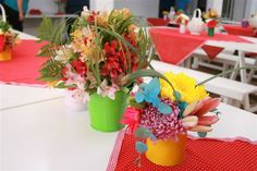 Multi coloured tins and buckets with assorted flowers