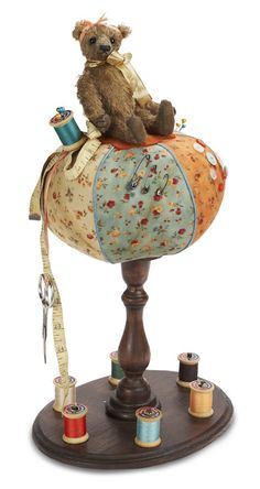 """from dollmasters.com,   Orange & Blue Pin Cushion Teddy on Stand - Features a small chocolate-brown bear resting atop a large blue and gold pin-cushion with a tall oval wooden base. 17""""."""