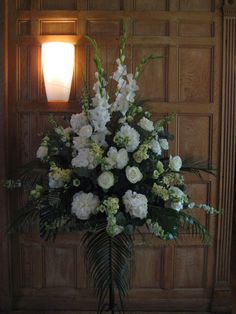 a large pedestal arrangement with tall gladiolus, white hydrangea, white peonies and white avalanche roses