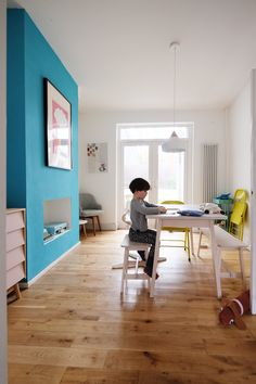In the dining room, the table and bench are IKEA and the yellow chairs are Habitat. Turquoise paint in the dining room is Laurence Llewelyn-Bowen.