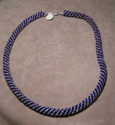 "N038 - $35+ S*H  -- Is a ""Russian spiral"" necklace made of silver lined crystal and opaque cobalt seed beads, with Sterling Silver bead caps and a silver plated brass fishhook clasp for a total length of 20"""