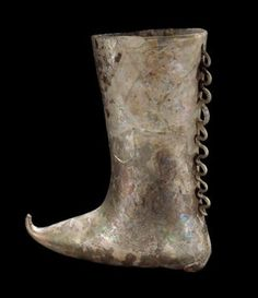 Islamic glass vessel shaped like a boot, 9th-12th century A.D. Possibly central Asia,  colorless, blown and applied, vessel shaped like calf boot, 14.2 cm high. Corning museum of glass