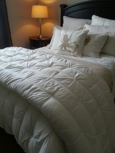 Beachy bedroom -- black headboard, white comforter, add tan element(s)