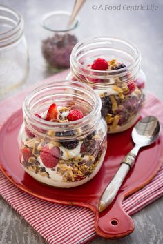 Breakfast parfaits with Greek yogurt, fresh berries, granola and cocoa nibs. Simple to assemble and easy to transport when made in canning jars.