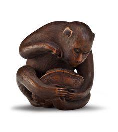 SIGNED TOMOKAZU, EDO PERIOD (19TH CENTURY) A carved wood netsuke of a monkey