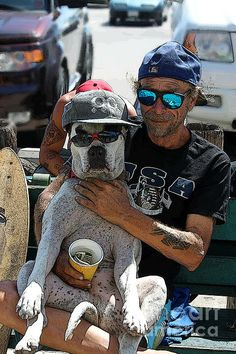 A photograph of a Man and his Dog, a Pit Bull, put to work begging on the Boardwalk at Venice Beach, California. He was very happy and content with life.